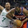 Photo - Washington Wizards' Nene Hilario (42) drives past Boston Celtics' Jared Sullinger (7) in the first quarter of an NBA basketball game in Boston, Saturday, Dec. 21, 2013. (AP Photo/Michael Dwyer)