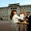 The Queen\'s Press Secretary Ailsa Anderson with Badar Azim, a footman, places an official document to announce the birth of a baby boy, at 4.24pm to the William and Kate, the Duke and Duchess of Cambridge at St Mary\'s Hospital, in the forecourt of Buckingham Palace in London Monday July 22, 2013. The child is now third in line to the British throne. (AP Photo/John Stillwell, Pool)