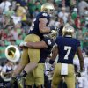 Notre Dame\'s Troy Niklas (85) celebrates with teammates Nick Martin and TJ Jones (7) after scoring on a 30-yard touchdown reception during the second half of an NCAA college football game against Oklahoma, Saturday, Sept. 28, 2013, in South Bend, Ind. Oklahoma defeated Notre Dame 35-21. (AP Photo/Darron Cummings) ORG XMIT: INDC121