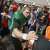OSU\'s J.W. Walsh places a hat back on a young fan while signing autographs for fans after Oklahoma State\'s Orange Blitz football practice at Boone Pickens Stadium in Stillwater, Okla., Saturday, April 5, 2014.