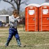"Photo - This small cowboy enjoys a cup of homemade ice cream as he walks past bright orange portable toilets. Oklahoma Cooperative Extension Service celebrated their 100th anniversary with a Whistle Stop and Festival on Saturday, April, 12, 2014 at the Rock 'N Rail yard near Highway 66 in Wellston, Oklahoma.  ""In the early 1900s, trains were the modern way to travel and early Extension agents were allowed to 'ride the rails', going from town to town presenting demonstrations  and showing people how they might improve the quality of their lives by making use of the latest science-proven advances, practices and products,"" said James Trapp. OCES associate director. A train coming into town was sometimes referred to  as a ""county fair on wheels."" As part of its centennial celebration, Extension conducted an historic reenactment  of the type of whistle stop tours that would have occurred   in 1914. Visitors  at the festival were given the opportunity to visit a variety of tents and booths offering demonstrations and hands-on activities representative of Extension programs. Photo by Jim Beckel, The Oklahoman"