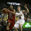 Photo - Lamar guard Donley Minor (22) drives to the basket past Baylor's Brady Heslip (5) in the first half of an NCAA college basketball game on Wednesday, Dec. 12, 2012, in Waco, Texas. (AP Photo/Tony Gutierrez)