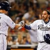 Photo - San Diego Padres' Rene Rivera is congratulated by Seth Smith, left, after scoring from third on a sacrifice fly by Alexi Amarista against the St. Louis Cardinals in the third inning of a baseball game Tuesday, July 29, 2014, in San Diego. (AP Photo/Lenny Ignelzi)