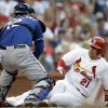 St. Louis Cardinals\' Allen Craig, right, is tagged out at home by Texas Rangers catcher A.J. Pierzynski during the first inning of a baseball game on Friday, June 21, 2013, in St. Louis. (AP Photo/Jeff Roberson)