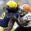 Photo - Green Bay Packers running back Eddie Lacy (27) is tackled by Cleveland Browns' Tashaun Gipson during the first half of an NFL football game Sunday, Oct. 20, 2013, in Green Bay, Wis. (AP Photo/Tom Lynn)