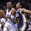 Photo - Oklahoma City Thunder guard Russell Westbrook, left, drives past Utah Jazz guard Trey Burke (3) in the second quarter of an NBA basketball game in Oklahoma City, Sunday, March 30, 2014. (AP Photo/Sue Ogrocki)