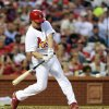 Photo - St. Louis Cardinals' Mark Ellis hits a two-run single against the Chicago Cubs in the second inning in a baseball game, Monday, May 12, 2014, at Busch Stadium in St. Louis. (AP Photo/Bill Boyce)