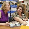 Photo - PC School's Ann Bradshaw, left, with Federal Programs, and Melissa Ahlgrim, the Elementary Language Arts Curriculum Coordinator for Putnam City Schools, look over curriculum at the administration building in Oklahoma City, OK, Friday, May 30, 2014,  Photo by Paul Hellstern, The Oklahoman
