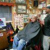 Philip Dunlap watches the Inauguration of President Barack Obama while Phillip Gates cuts his hair at Gates Barber Shop at NE 26th and Martin Luther King Blvd. in Oklahoma City. January 20, 2009. BY STEVE GOOCH, THE OKLAHOMAN.
