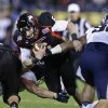 Photo - Northern Illinois quarterback Jordan Lynch plows through the Utah State defense for first down during the first half of the Poinsettia Bowl NCAA college football game Thursday, Dec. 26, 2013, in San Diego. (AP Photo/Lenny Ignelzi)