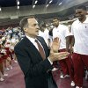 Photo - New University of Oklahoma men's basketball coach walks by his new team before being introduced as the new University of Oklahoma men's college basketball coach on Monday, April 4, 2011, in Norman, Okla. Photo by Chris Landsberger, The Oklahoman