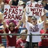 Cabria Turang, left, and Tress Way hold signs supporting OU softball player Brianna Turang (2) during an NCAA softball game in the Women\'s College World Series between Oklahoma and Texas at ASA Hall of Fame Stadium in Oklahoma City, Saturday, June 1, 2013. Cabria Turang is Brianna Turang\'s sister, and Tress Way, a former OU football player, is engaged to Brianna Turang. Oklahoma won 10-2 in five innings. Photo by Nate Billings, The Oklahoman