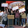 FILE- In this Feb. 22, 2006, file photo, the eight winners of the $365 million Nebraska Powerball lottery hold up their ceremonial checks at a news conference in Lincoln, Neb. As the drawing for a $500 million Powerball jackpot approaches, Wednesday, Nov. 28, 2012, past winners of mega-lottery drawings and financial planners have some advice: stick to a budget, invest wisely, learn to say no and be prepared to lose friends while riding an emotional roller-coaster. (AP Photo/Nati Harnik, File)