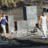 Regina and Sean Cox walk through what remains of the home and outbuilding of Regina\'s brother\'s mobile home as they see for the first time the damage from Friday\'s wildfire on Saturday, Aug. 4, 2012, in Slaughterville, Okla. Photo by Steve Sisney, The Oklahoman