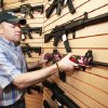 Photo - Mike Blackwell, owner of Big Boy's Guns and Ammo, places a pink Smith & Wesson rifle on the shelf at the store in Oklahoma City. Photo by Steve Gooch, The Oklahoman