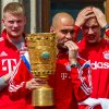 Photo - Bayern Munich's  head coch Pep Guardiola holds the trophy, as the  team of Bayern Munich celebrates on the balcony of the Munich city hall Sunday May 18, 2014. Bayern Munich won the soccer cup final against Borussia Dortmund  in Berlin on Saturday.  (AP Photo/dpa, Marc Mueller)