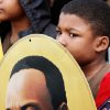 Renzo Byrd, 7, holds an oval portrait of Martin Luther King, Jr. while standing next to his mother and others outside the Freedom Center for brief speeches and songs before they begin the Silent March; it is one of several events in the Oklahoma City area that allowed local residents to observe the national holiday honoring slain civil rights leader, Dr. Rev. Martin Luther King, Jr. on Monday, Jan. 16, 2012, Photo by Jim Beckel, The Oklahoman