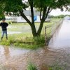 "Photo - Rural resident Rodney Miller watches Monday as flood waters flow around and up to his home located four miles southwest of Ponca City along Riverview Road. ""I've never seen the water this high,"" Miller said. His home sits just east of Bois d'Arc Creek. (Poncan City News Photo by Rolf Clements)"