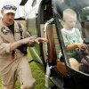 Trooper Drew Hamilton, pilot, explains the operation of the Oklahoma Highway Patrol\'s helicopter to parents while Gabriel Inman, 8, from Norman, sits at the controls during the annual