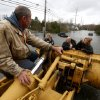 Brian Hajeski, 41, left, rides on the extension of a front loader as he helps neighbors get out of their flooded home and into dry land the morning after superstorm Sandy rolled through, Tuesday, Oct. 30, 2012, in Brick, N.J. Sandy, the storm that made landfall Monday, caused multiple fatalities, halted mass transit and cut power to more than 6 million homes and businesses. (AP Photo/Julio Cortez) ORG XMIT: NJJC113