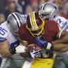 Photo - Washington Redskins running back Alfred Morris is tackled by Dallas Cowboys nose tackle Sean Lissemore (95) and defensive end Jason Hatcher (97) during the first half of an NFL football game Sunday, Dec. 30, 2012, in Landover, Md. (AP Photo/Alex Brandon)