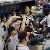 Photo - Houston Astros' Chris Carter, right, celebrates with coaches and teammates after hitting a two-run home run off Philadelphia Phillies starting pitcher Sean O'Sullivan during the third inning of an interleague baseball game, Thursday, Aug. 7, 2014, in Philadelphia. (AP Photo/Matt Slocum)