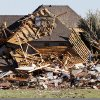 Sue Lord is dwarfed by the debris from her home, which is piled up on the neighbor\'s home, following a tornado in Woodward, Okla., Sunday, April 15, 2012. Lord was in the home when the tornado struck, but was not injured. (AP Photo/Sue Ogrocki)