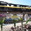Photo - Bouquets of flowers line a fence in front of the burned-out Mariner's Cove Motor Inn in Point Pleasant Beach N.J. on Monday March 24, 2014. Four people died in a fire at the motel early Friday.(AP Photo/Wayne Parry)