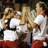 OU catcher Jessica Shults (18), left, and pitcher Keilani Ricketts (10) celebrate with the rest of the Sooners after an NCAA softball game in the Women\'s College World Series between Oklahoma and Michigan at ASA Hall of Fame Stadium, Thursday, May 30, 2013. OU won, 7-1. Photo by Nate Billings, The Oklahoman