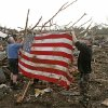 Clark Gardner, at left, and another man place an American flag on debris in a neighborhood off of Telephone Road in Moore, Okla., after a tornado moved through the area on Monday, May 20, 2013. Photo by Bryan Terry, The Oklahoman