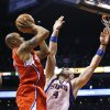Los Angeles Clippers\' Caron Butler, left, drives to the basket to score against Phoenix Suns\' Marcin Gortat (4), of Poland, during the first half in an NBA basketball game on Thursday, Jan. 24, 2013, in Phoenix. (AP Photo/Ross D. Franklin)