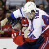Photo - Washington Capitals right wing Tom Wilson, left, ducks a punch by New York Rangers defenseman Justin Falk as they fight in the first period of an NHL hockey game, Wednesday, Oct. 16, 2013, in Washington. (AP Photo/Alex Brandon)