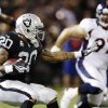 Oakland Raiders running back Darren McFadden (20) carries the ball as Denver Broncos defensive tackle Justin Bannan, right, watches during the second quarter of an NFL football game in Oakland, Calif., Thursday, Dec. 6, 2012. (AP Photo/Marcio Jose Sanchez)