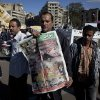 An Egyptian protester carries a copy of Al Wafd newspaper front page that reads in Arabic