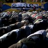 Egyptian protesters opposing president Mohammed Morsi attend Friday prayers beneath with a poster depicting protesters killed in the Egyptian revolution, at Tahrir Square, Cairo, Egypt, Friday, Dec. 7, 2012. Arabic on the poster reads their names from right