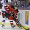 New Jersey Devils\' Andy Greene (6) keeps the puck away from New York Rangers\' Mats Zuccarello, of Norway, during the first period of an NHL hockey game game Saturday, March 22, 2014, in Newark, N.J. (AP Photo/Mel Evans)