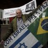 Photo - A Jewish demonstrator holds up the flags of Brazil and Israel with a sign that reads in Portugual
