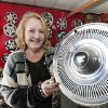 Photo - Sandra Mullins, who runs Hubcap World in Oklahoma City, is shown with a 1971 Buick Wildcat hubcap. PHOTO BY David McDaniel, The Oklahoman