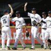 Photo - Seattle Mariners players share congratulations after defeating the Los Angeles Angels in a baseball game on Sunday, July 14, 2013, in Seattle. The Mariners won 4-3. (AP Photo/Elaine Thompson)