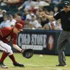 Photo - Arizona Diamondbacks' Jordan Pacheco, left, fields a ground ball hit by Colorado Rockies' Justin Morneau as umpire Mark Ripperger, right, calls the ball fair during the first inning of a baseball game Sunday, Aug. 31, 2014, in Phoenix. (AP Photo/Ross D. Franklin)
