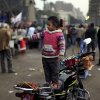 An Egyptian girl wears national flag colors painted on her face as she stands on her father\'s motorcycle during a demonstration in Tahrir square in Cairo, Egypt, Friday, Dec. 14, 2012. Opposing sides in Egypt\'s political crisis were staging rival rallies on Friday, the final day before voting starts on a contentious draft constitution that has plunged the country into turmoil and deeply divided the nation.(AP Photo/Khalil Hamra) ORG XMIT: KH101