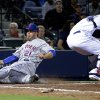 Photo - New York Mets' Lucas Duda, left, slides past the tag of Atlanta Braves catcher Evan Gattis to score off a single by teammate Ruben Tejada in the eighth inning of baseball game, Tuesday, April 8, 2014, in Atlanta. (AP Photo/David Goldman)