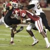 Missouri\'s T.J. Moe (28) is upended by Oklahoma\'s Javon Harris (12) during the college football game between the University of Oklahoma Sooners (OU) and the University of Missouri Tigers (MU) at the Gaylord Family-Memorial Stadium on Saturday, Sept. 24, 2011, in Norman, Okla. Photo by Steve Sisney, The Oklahoman