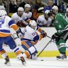 New York Islanders\' Andrew MacDonald (47) watches as right wing Colin McDonald (13) compete for control of the puck against Dallas Stars\' Jamie Benn (14) in the first period of an NHL hockey game, Sunday, Jan. 12, 2014, in Dallas. (AP Photo/Tony Gutierrez)