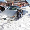Photo - David Rogers digs snow away from his wife's car on Friday.  Photo by Jim Beckel, The Oklahoman