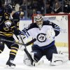 Photo - Buffalo Sabres center Tyler Ennis (63) watches the rebound bounce off the shoulder of Winnipeg Jets goaltender Ondrej Pavelec, of Czech Republic, during the first period of an NHL hockey game in Buffalo, N.Y., Tuesday, Dec. 17, 2013. (AP Photo/Gary Wiepert)