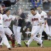 Photo - Cleveland Indians' Zack Walters , right, is mobbed by teammates after hitting a game-winning solo home run off Arizona Diamondbacks relief pitcher Randall Delgado in the ninth inning of the first baseball game of a doubleheader, Wednesday, Aug. 13, 2014, in Cleveland. The Indians defeated the Diamondbacks 3-2. (AP Photo/Tony Dejak)