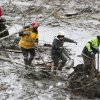 Search and rescue teams navigate the wet, muddy terrain at the west side of the mudslide on Highway 530 near mile marker 37 on Sunday, March 30, 2014, in Arlington, Wash. Periods of rain and wind have hampered efforts the past two days, with some rain showers continuing today. (AP Photo/Rick Wilking, Pool)