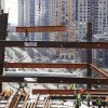 FILE - In this March 25, 2010 file photo, an ironworker walks on a beam as he guides another beam suspended from a crane at One World Trade Center construction site in New York. (AP Photo/Mark Lennihan, File)