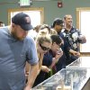 Customers look at a glass case containing pipes and information on recreational marijuana at Top Shelf Cannabis, Tuesday, July 8, 2014, in Bellingham, Wash., on the first day of legal sales in the state. (AP Photo/Ted S. Warren)